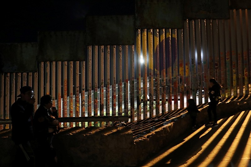 People in silhouette are seen in front of the U.S. and Mexico border fence at Friendship Park in Tijuana, Mexico, Jan. 23, 2019. (Reuters Photo)
