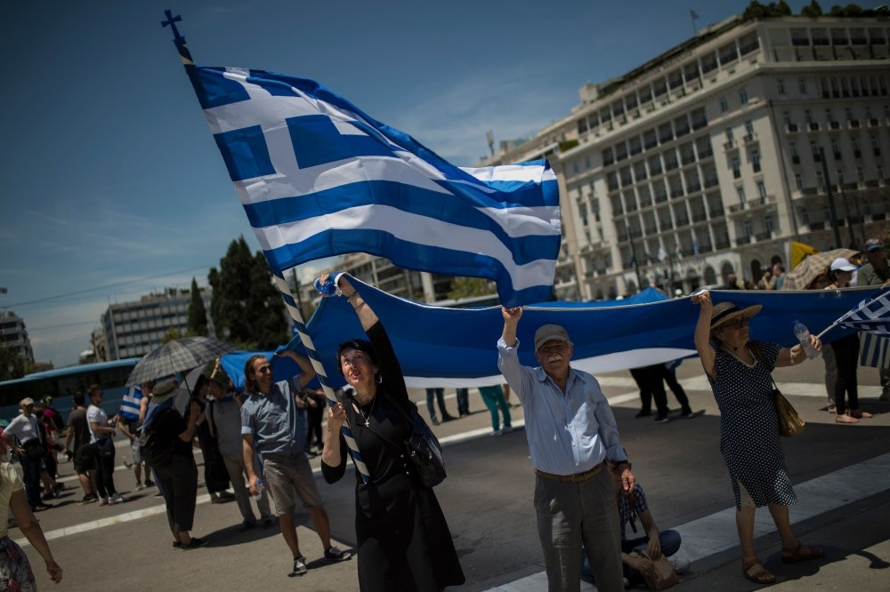 People protesting the Macedonia name agreement, hold a Greek flag, Athens, June 15.