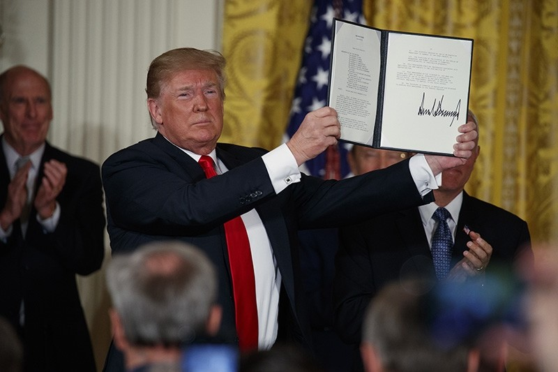 President Donald Trump shows off a ,Space Policy Directive, after signing it during a meeting of the National Space Council in the East Room of the White House, Monday, June 18, 2018, in Washington. (AP Photo)