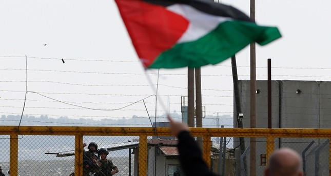 A Palestinian protester waves his national flag in front of Israeli security forces as they mark Land Day outside the compound of the Israeli-run Ofer prison near Betunia in the Israeli occupied West Bank on March 30, 2016. AFP Photo