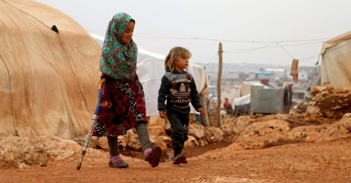 9-year-old Syrian girl Maya Meri seen walking in a refugee camp in Syria thanks to prosthetic legs she received in Turkey last year. (AA Photo)
