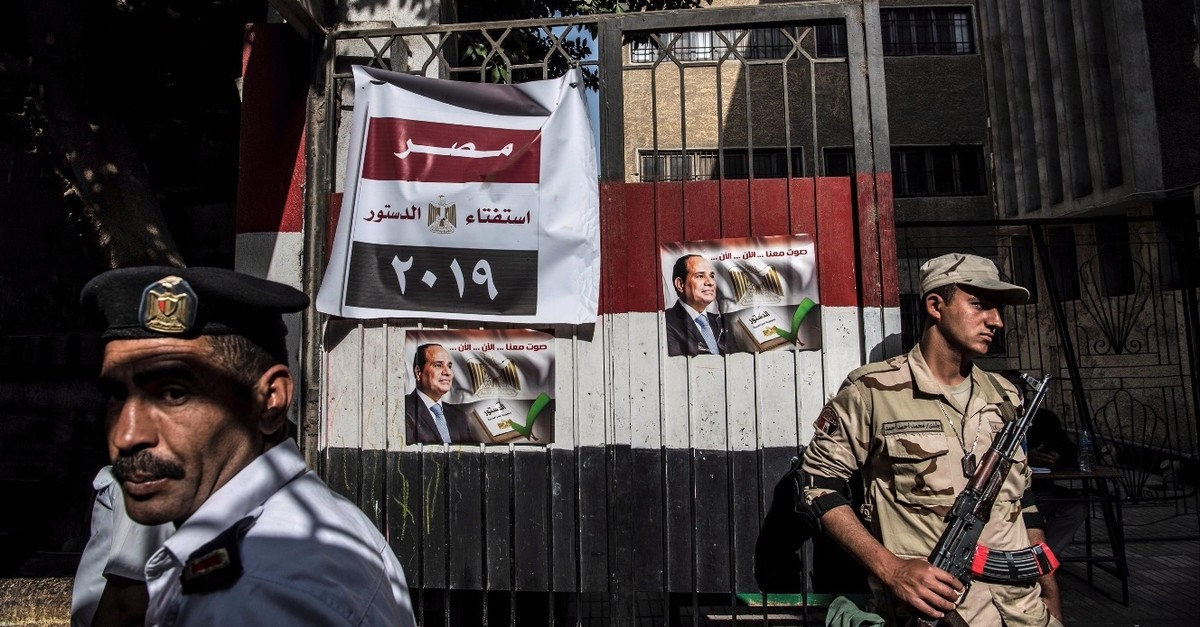 An Egyptian soldier and a policeman stand guard a polling station during the third day of a referendum on constitutional amendments in Cairo, April 22, 2019.