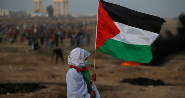 A woman holds a Palestinian flag during a protest calling for the lifting of the Israeli blockade on Gaza and demanding the right to return to their homeland, Oct. 19.