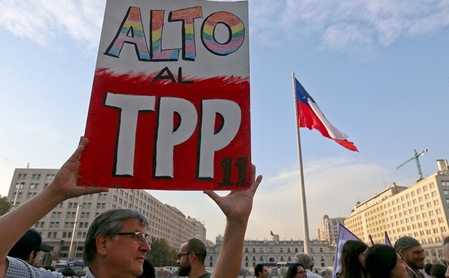A man holds a sign against the signing of the Trans-Pacific Partnership, TPP, during a demonstration outside La Moneda presidential palace, in Santiago, Chile, Wednesday, March 7, 2018. (AP Photo)