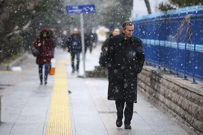 Ankara residents walk through morning snowfall. (AA)