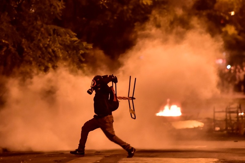 A protestor throws a chair in Athens on November 17, 2018, during clashes with anti-riot police following a rally  commemorating the 1973 students uprising against the US-backed military junta. (AFP Photo)