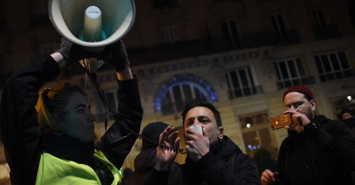 A protester speaks in a megaphone during a demonstration in front of the Bouffes du Nord theatre in Paris on January 17, 2020 as French President attends a play. (AFP Photo)