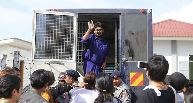 Myanmar freelance journalist Aung Naing Soe waves to his family from a prison van as he leaves after a hearing on his trial at Zabu Thiri Court in Naypyitaw, Myanmar, Nov. 16, 2017. (EPA Photo)