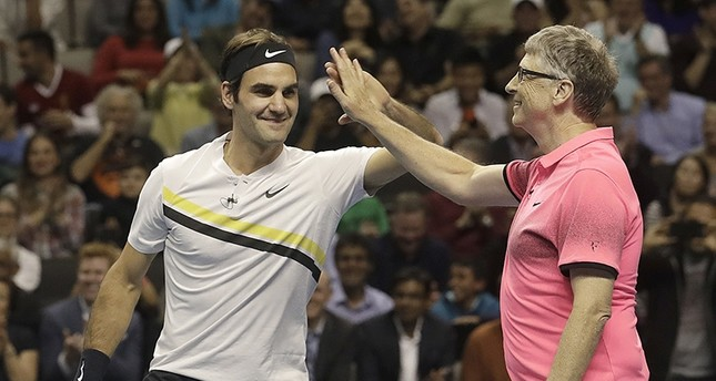 Roger Federer, of Switzerland, left, celebrates with partner Bill Gates as they play an exhibition tennis match against Jack Sock and Savannah Guthrie in San Jose, Calif., (AP Photo)