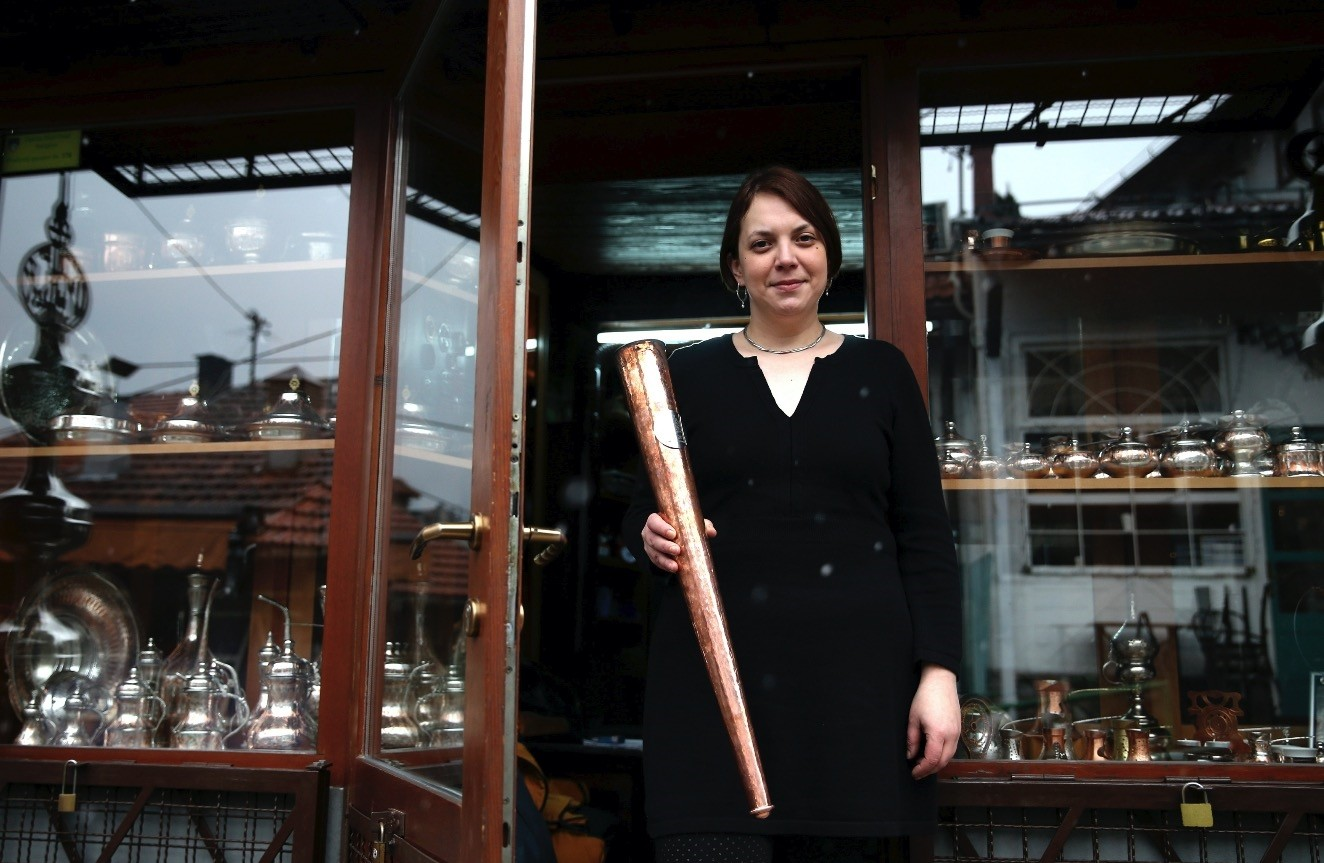 Nermina Alic, poses for a photo with the Olympic flame torch that she designed for the upcoming European Youth Olympic Winter Festival in Sarajevo, Bosnia-Herzegovina, Feb. 4, 2019.