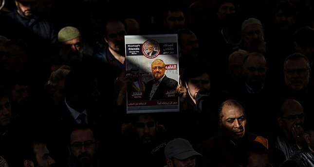 In this Nov. 16, 2018 photo, a person holds a banner of Jamal Khashoggi during a symbolic funeral prayer for the Saudi journalist, killed and dismembered in the Saudi consulate in Istanbul in October, at the courtyard of Fatih mosque. (AFP Photo)