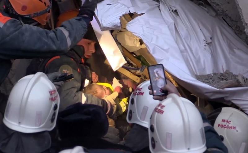 This handout picture released by The Russian Emergency Situations Ministry on January 1, 2019, shows emergency officers transporting a baby surviver after a gas explosion rocked a residential building in Magnitogorsk. (AFP Photo)