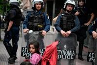 عناصر من الشرطة اليونانية أمام مظاهرة لطالبي اللجوء أمام مكاتب الاتحاد الأوروبي الفرنسية