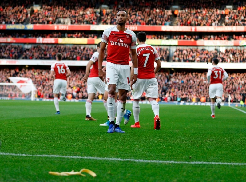 A banana thrown from the crowd is seen at the side of the pitch as Arsenal's Gabonese striker Pierre-Emerick Aubameyang (C) celebrates after scoring the opening goal (AFP Photo)