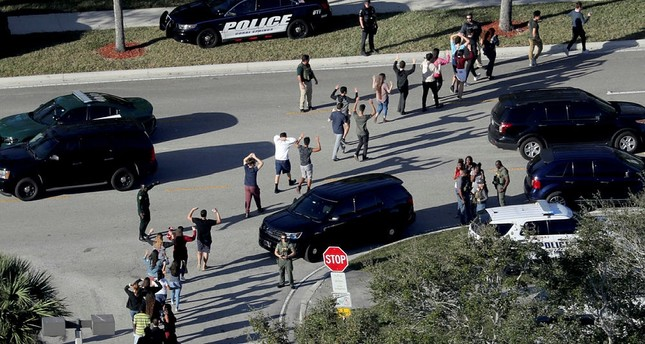 In this Feb. 14, 2018 file photo, students hold their hands in the air as they are evacuated by police from Marjory Stoneman Douglas High School in Parkland, Fla., after a shooter opened fire on the campus. (AP Photo)