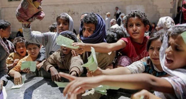 In this April 13, 2017 file photo Yemenis present documents in order to receive food rations provided by a local charity in Sanaa, Yemen. (AP Photo)