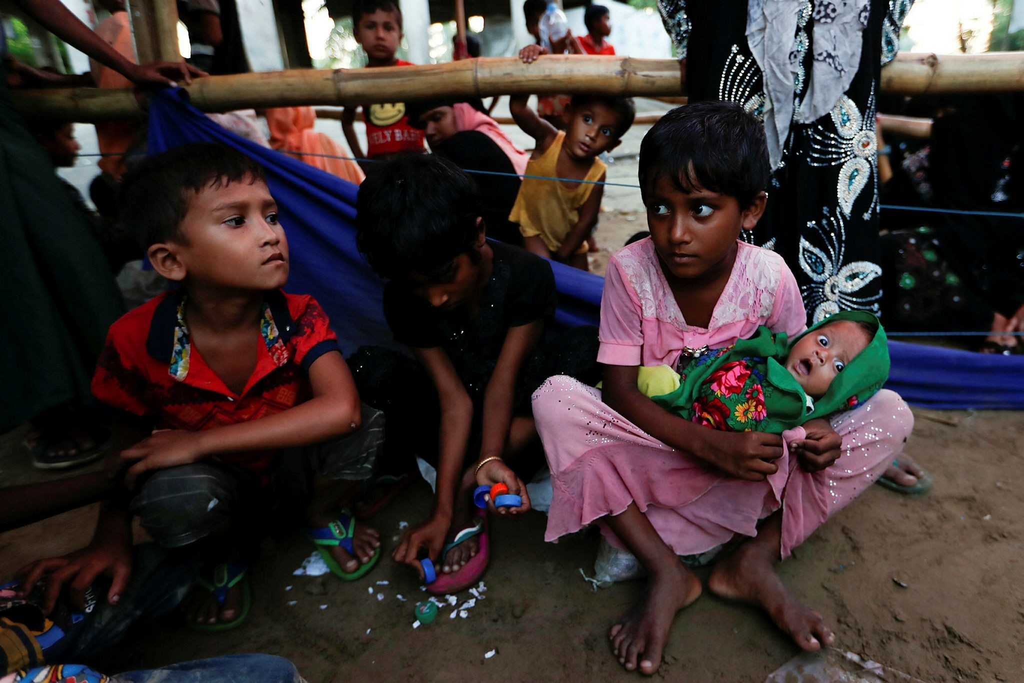 Rohingya refugee children sit as they wait for permission from the Bangladeshi military to continue at a registration center in Teknaf, Oct. 15.