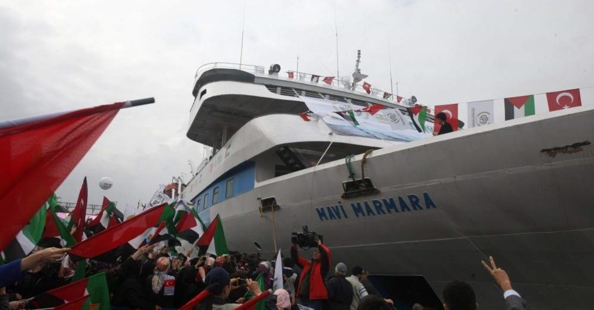 In this file photo taken on Dec. 26, 2010, people holding Turkish and Palestinian flags cheer as the Mavi Marmara ship arrives back in Istanbul, Turkey. (AP Photo)