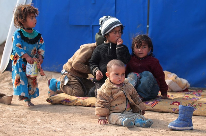Displaced Iraqi children sit at the Al-Agha camp where Iraqi families from the nearby villages of Tal Afar are taking shelter as Iraqi forces continue their military operation in Mosul on February 16, 2017. (AFP Photo)