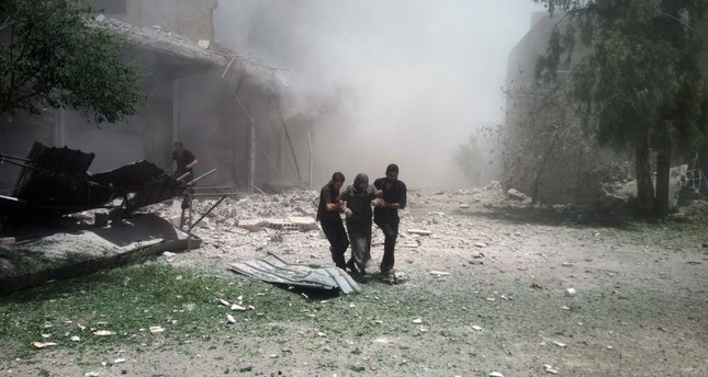A cloud of dust is seen after a building collapsed as a Syrian woman is helped to leave the area following air strikes in the town of Kfar Batna, Damascus.