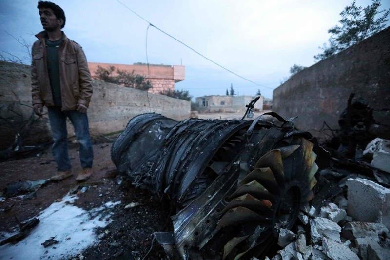 A picture taken on February 3, 2018, shows a Syrian man standing next to a burnt jet engine at the site of a downed Sukhoi-25 fighter jet in the the Syrian city of Saraqib, southwest of Aleppo. (AFP Photo)