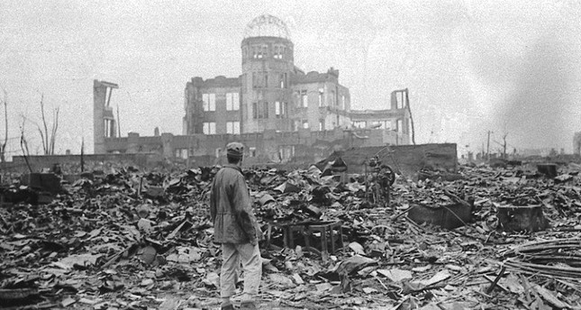 An allied correspondent stands in a sea of rubble before the shell of a building that once was a movie theater in Hiroshima, Aug. 6, 1945 - three days before the another deadly attack in Nagasaki, Japan.