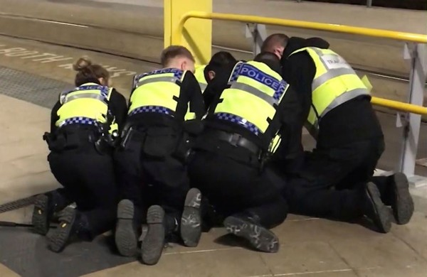 UGC issued by PA shows Police restraining a man after he stabbed three people at Victoria Station in Manchester, England, late Monday Dec. 31, 2018. (AP Photo)