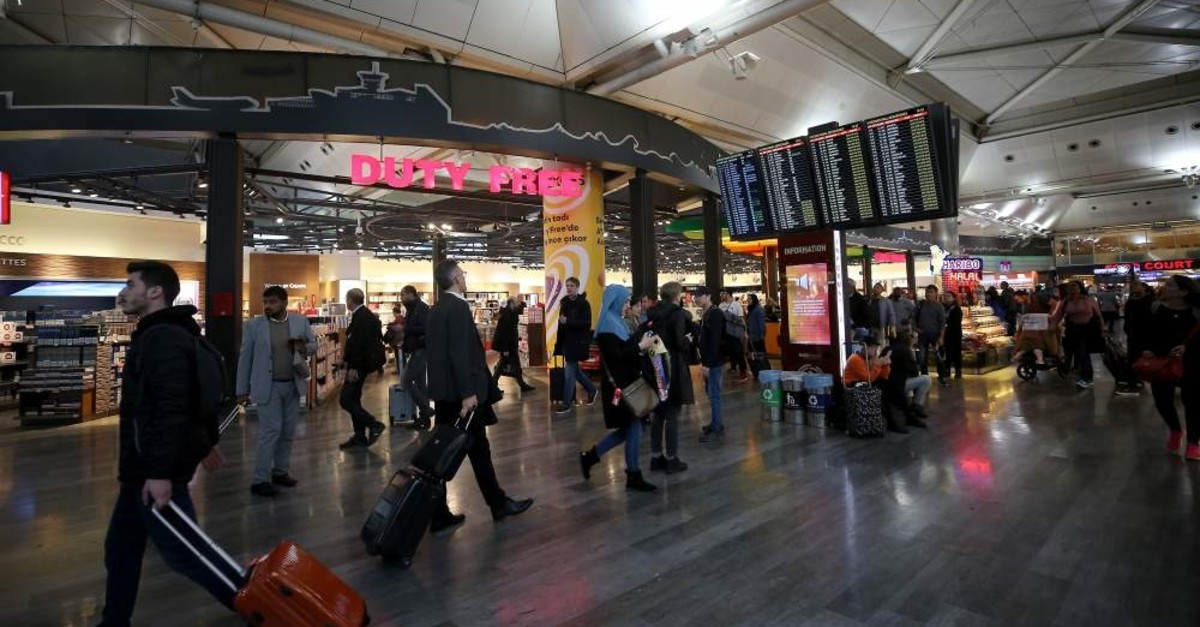 People walking in the Istanbul Airport with a flight information screen and duty free shop seen behind, Feb. 26, 2020. (AA Photo)