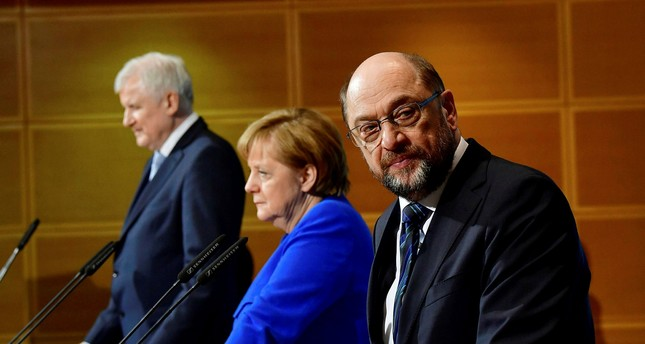 German leader of the SPD Martin Schulz (R) next to Chancellor Angela Merkel and Horst Seehofer of the CSU give a press conference after talks to form a new government at the SPD's Headquarters in Berlin, Jan. 12.