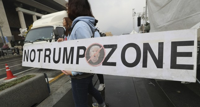 A woman holds a banner opposing President Trump's planned visit to the country near the U.S. Embassy in Seoul, South Korea, Nov. 3.