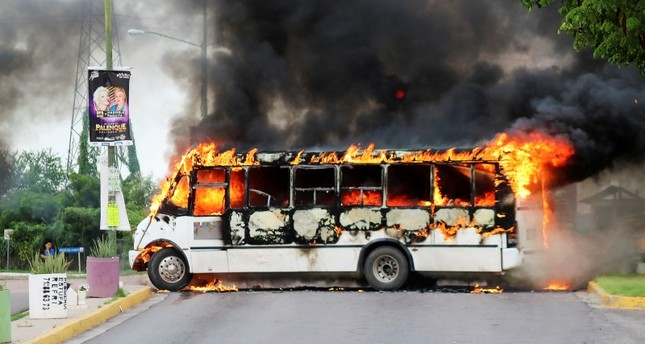 A burning bus, set alight by cartel gunmen to block a road, is pictured during clashes with federal forces following the detention of Ovidio Guzman, son of drug kingpin Joaquin El Chapo Guzman, in Culiacan, Mexico, Oct. 17, 2019. (Reuters Photo)