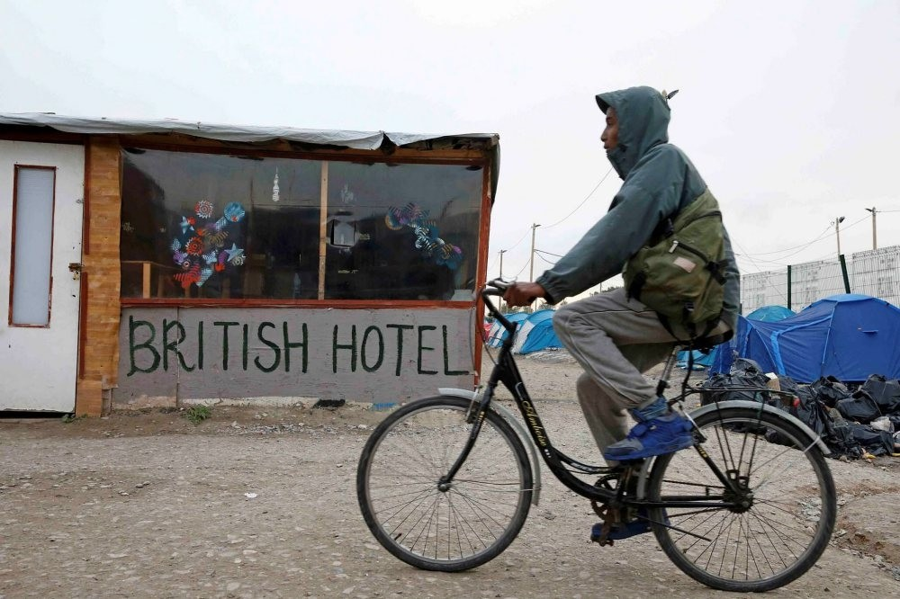 A migrant rides a bicycle in the northern area of the camp called the ,Jungle, in Calais, France, Sept. 26, 2016.