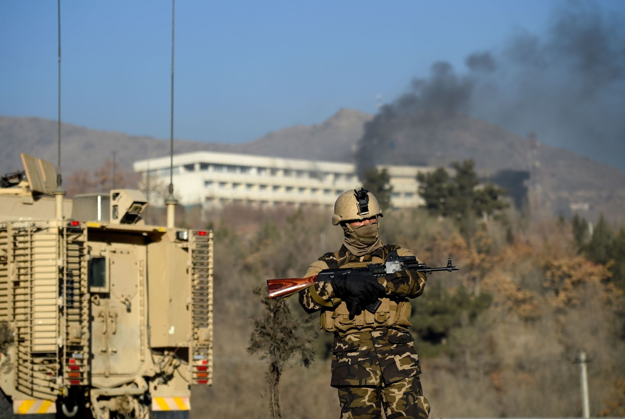 Afghan security personnel standing guard as smoke billows from the Intercontinental Hotel during a fight between gunmen and Afghan security forces in Kabul. (AFP Photo)