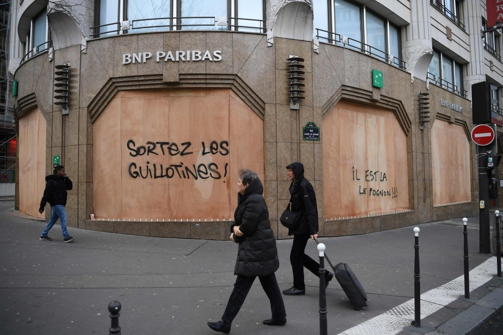 People walk past the protective wooden walls on a bank with a tag ,Get the guillotines out, and ,money is here, on Boulevard des Capucines in Paris, Dec. 9.