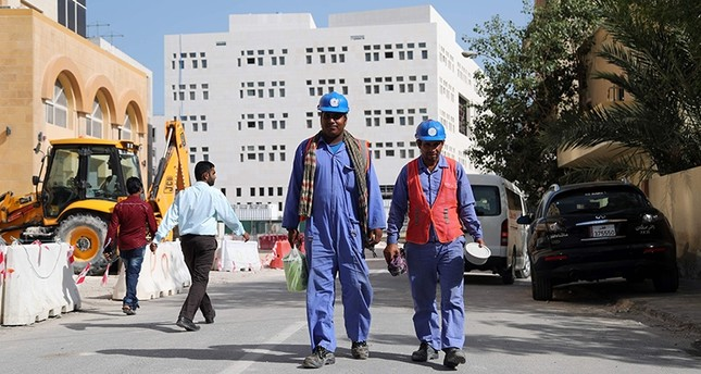 Migrant workers are seen walking next to a construction site in the Qatari capital Doha on December 6, 2016. AFP Photo