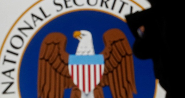 A man is silhouetted near logo of the U.S. National Security Agency (NSA) in this photo illustration taken in Sarajevo March 11, 2015.  (Reuters Photo)