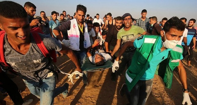 Palestinian paramedics carry an injured protester during demonstrations at the Israel-Gaza border, east of Khan Yunis in the southern Gaza Strip on August 24, 2018. (AFP Photo)