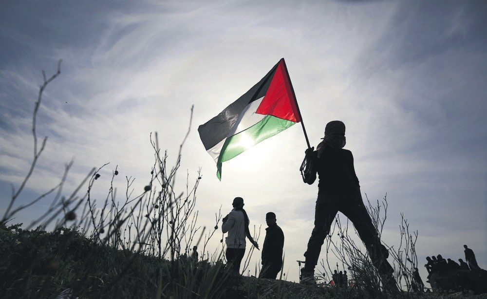 A Palestinian protester holds a Palestinian flag during clashes after Israeli troops attacked protesters near the border between Israel and the Gaza Strip, March 2.