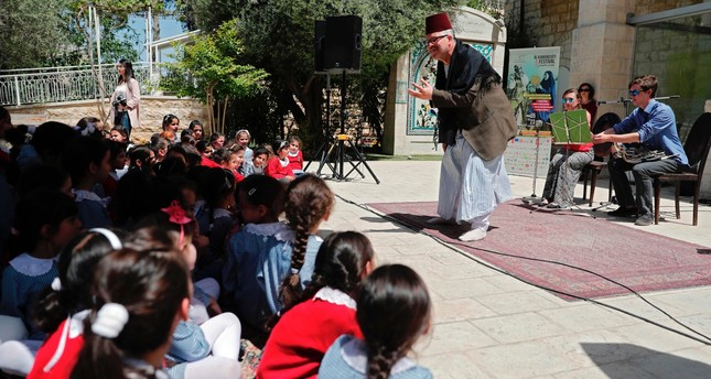 A Palestinian actor and two musicians perform in front of Palestinian schoolchildren during a festival organized by Palestinian musician Ramzi Aburedwan in east Jerusalem.