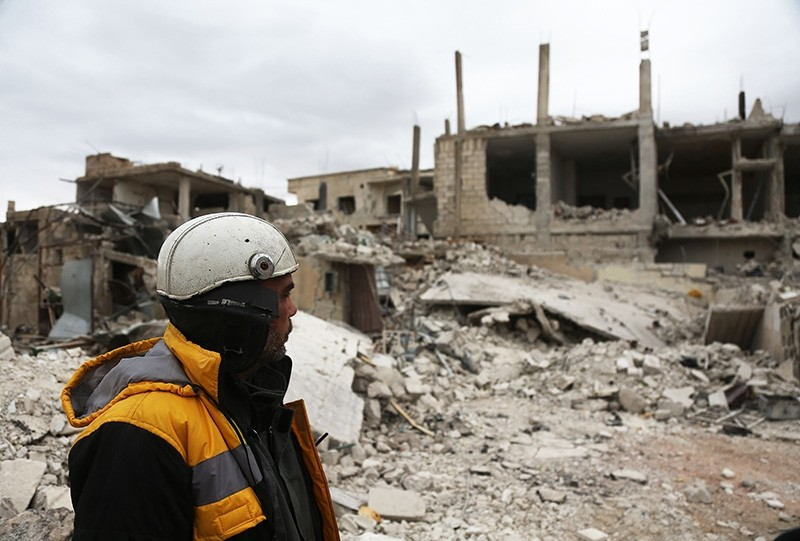 A White Helmets rescue worker looks out at destroyed buildings in the town of Medeira in Syria's opposition-held eastern Ghouta area on February 12, 2018. (AFP Photo)
