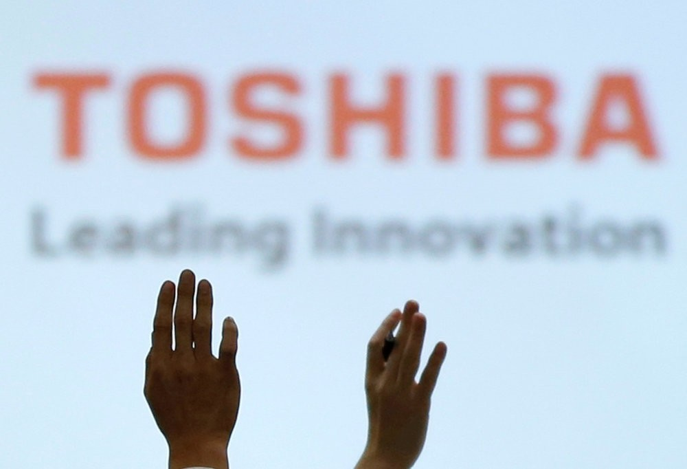 Reporters raise their hands for a question during a news conference by Toshiba Corp CEO Satoshi Tsunakawa and other senior sompany officials at the companyu2019s headquarters in Tokyo.
