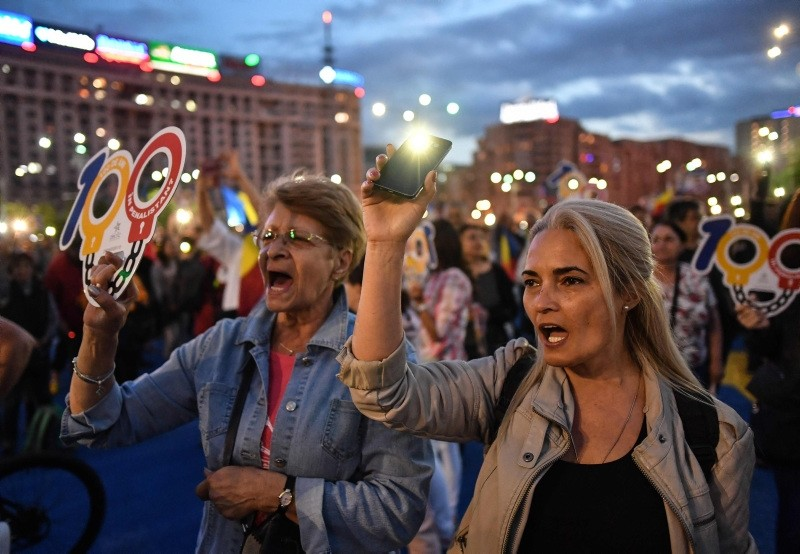 People use the light of their mobile phones and hold placards during a protest asking for the resignation of the Romanian Prime minister  on May 12, 2018 in front of the government headquarters in Bucharest. (AFP Photo)