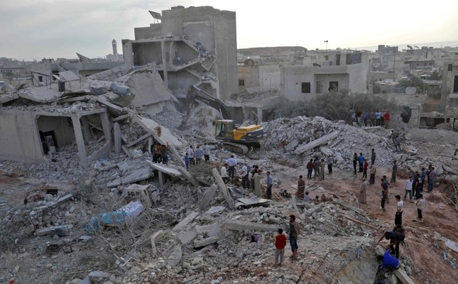 Syrians gather amidst destruction in Zardana, in the rebel-held northern Syrian Idlib province, in the aftermath of following air strikes in the area late on June 8, 2018. (AFP Photo)