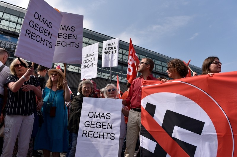 Elder ladies hold displays reading 'Grandmas against the right wing' during a demonstration against a gathering of far-right organizations commemorating the death anniversary Rudolf Hess in the district of Spandau in Berlin, Germany. (EPA Photo)