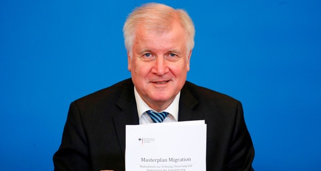 German Interior Minister Horst Seehofer poses with a copy of a Masterplan on Migration during a press conference in Berlin, on July 10, 2018. (AFP Photo)