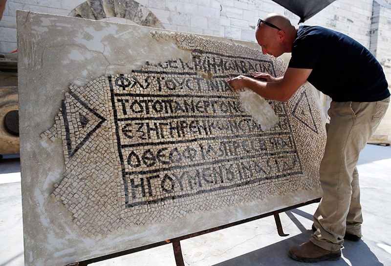 An archaeologist works on part of a 1,500-year-old mosaic floor bearing the names of Byzantine Emperor Justinian, at the Rockefeller Museum in Jerusalem, on August 23, 2017 (AFP Photo)