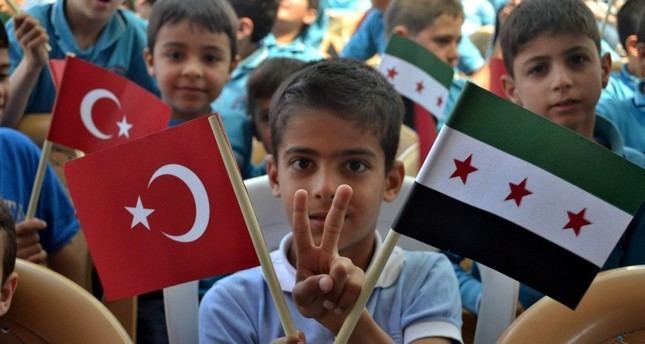 A Syrian student at a school for refugee children in the southern city of Hatay holds a Turkish and Syrian flag.