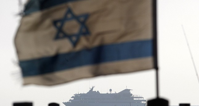 Israeli flag flutters in the wind as a naval vessel not seen escorts the Mavi Marmara, a Gaza-bound ship that was raided by Israeli marines, in this May 31, 2010 file picture. Reuters