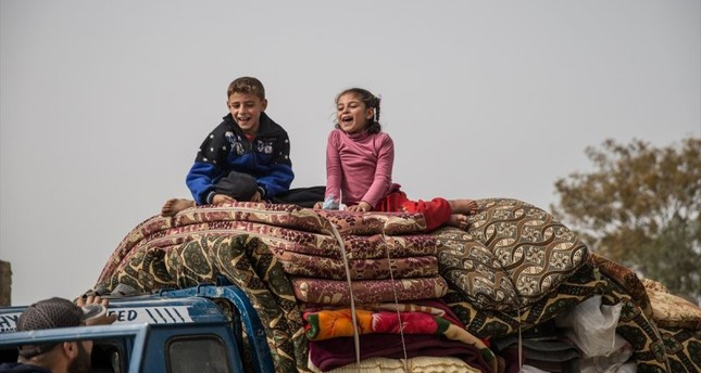 Syrian children are seen on a pickup truck with their family's belongings as they return to their homes in Afrin and Idlib, Syria on March 24, 2018.