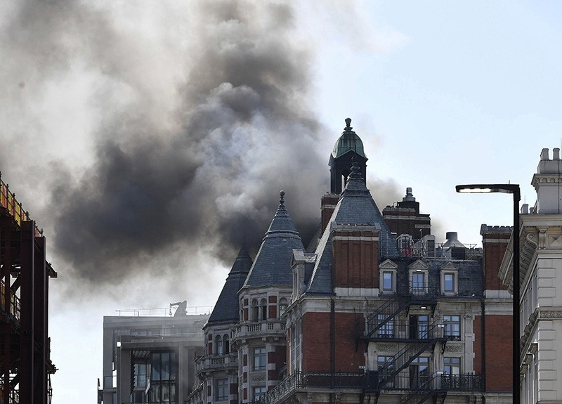 Smoke rises from a building in Knightsbridge, central London, as London Fire Brigade responded to a call of a fire in this upmarket location, Wednesday June 6, 2018. (AP Photo)